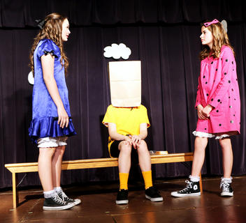 Lauren Bradshaw as Lucy and Elizabeth Russell as Sally don't even notice Charlie Brown (Joe Keith Shewmaker) with his disguise.