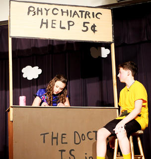 Lucy (Lauren Bradshaw) gives Charlie Brown (Joe Keith Shewmaker) some much-needed psychiatric evaluation at her pop-up stand.