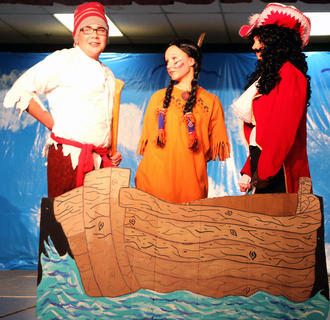 Smee (Carter Ballard) and Captain Hook (Ava Drury) capture Tiger Lily (Leah Wright) and prepare to throw her overboard.