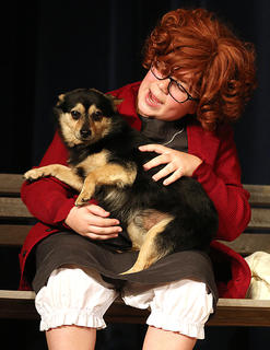 """Annie, played by Brooklyn Richardson, successfully escapes the orphanage and runs into a friendly stray dog. As she comforts him, she tells him of better days yet to come and sings """"Tomorrow."""" The dog catcher is after him, so she pretends the dog is hers by calling him Sandy."""