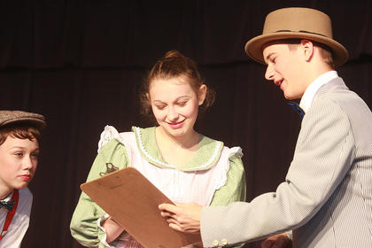 Harry Hill (Aaron Howard, right) gets Mrs. Paroo (Haley Ruley) to order a musical instrument and a band uniform for her son, Winthrop (Kaylee Thomas, left).