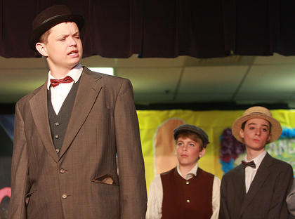 Traveling salesman Charlie Cowell (Ethan Sparks) lets the people (Luke Thomas, center, and Donavon Brockman) of River City know that Harry Hill isn't who he claims to be.