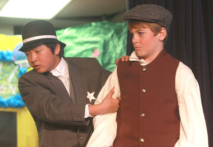 Constable Locke (Masa Goto) takes Tommy Djilas (Zachary Hunt) into custody, at least until Harold Hill says he'll take responsibility for Tommy.