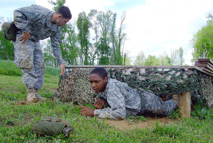 Shaquille Keene works his way to the end of the low crawl as Andrew Villanueva offers words of encouragement.