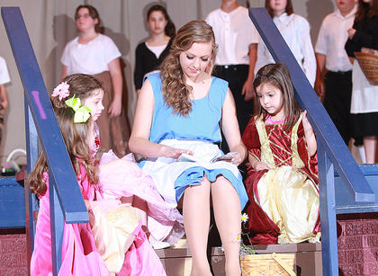 Belle (Leah Thompson) shares a story with three young villagers (Maddie Spalding, Jacklyn Farmer and Mia Mattingly).