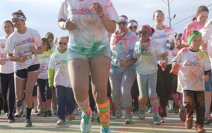 Hundreds of runners take off at the starting line during one of three waves of runners who participated in the Color in Motion 5K on May 17.