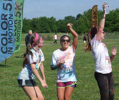 From left, Bailey Spalding, Amelia Bradshaw and Morgan Osbourne dance in the festival area after finishing the Color in Motion 5K.