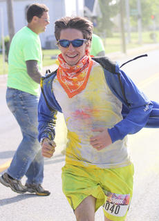 Jacob Scott of Edmonson County is one of the first to make it through the first color stop on Main Street. Lebanon Tourist Commission Chairman Brad Lanham helps douse runners in color.