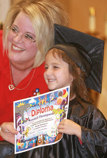 Preschooler Kendall Thompson accepts her diploma from teacher Chasity Smith.