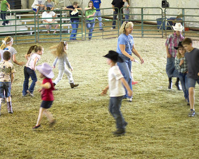 Kids demonstrate their horse gaits in a circle around Cheryl May.