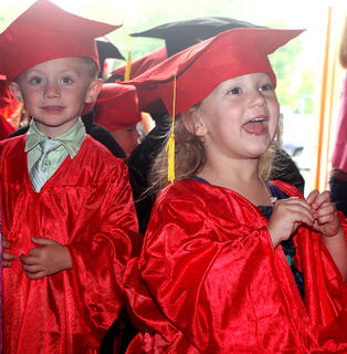 St. Augustine preschoolers Soliel Anderson and Cash Bickett are anxious to begin graduation ceremonies Friday afternoon.
