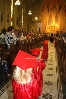 Preschoolers file, one by one, into the St. Augustine Catholic Church for their graduation ceremony.
