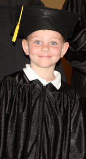 Hayden Lanham is bright eyed and all smiles during preschool graduation Friday at St. Augustine Catholic Church.