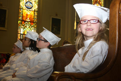 Leanna Jeffries smiles for the camera as she waits to receive her kindergarten diploma.