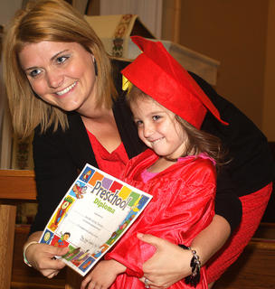 Kendall Thompson shows her excitement as she accepts her diploma from her preschool teacher Hope Newton-Dougherty.