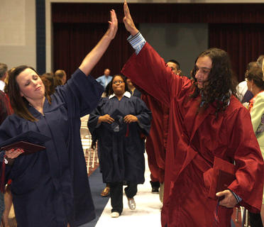 Amber Lee Blanford and Aaron Keith Brady share a high five as they exit the Robey Dome at the end of the graduation ceremony.
