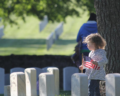 The annual Memorial Day program was held Sunday, May 26, at Lebanon National Cemetery. Amber Spurling, 3, helps place flags at each grave site at the Lebanon National Cemetery.