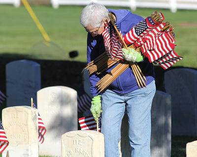 Christy Lee was there early and began placing flags in the first section of the cemetery.