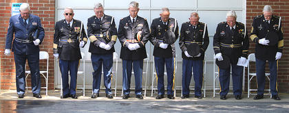 Members of the Marion County Veterans Honor Guard bow their heads in prayer.