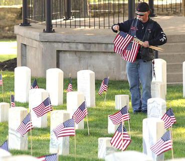 Joe Robinson places flags at the headstones in Lebanon National Cemetery.