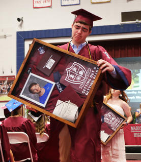 Austin Smith prepares to give a memorial shadow box to the family of Joseph Michael Robey, who passed away this school year in a car accident. Robey would have graduated alongside the rest of his class on Saturday.