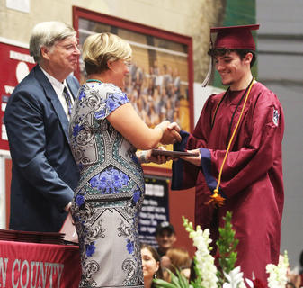 James Cody Abell receives his diploma from school board members Carrie Truitt and David Cox.