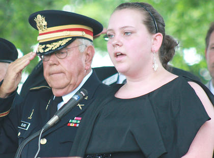 Elli Evans sings the national anthem as Col. Frank Bland, the master of ceremonies for the program, salutes.