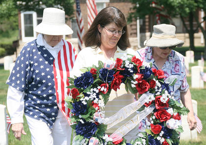 Tracy Osborne, center, places a wreath on behalf of the family of the last veteran interred at Lebanon National Cemetery. She was escorted by Janet Moore, left, and Anne Browning. Osborne is the daughter of the late Sgt. First Class Joseph Ryan.