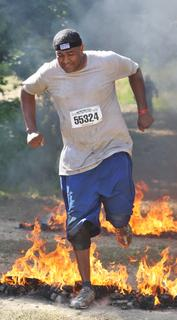 Desmond Spalding jumps through the Warrior Roast, one of the obstacles during the Warrior Dash.