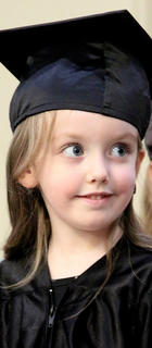 Hadley Fisher, 4, excitedly awaits her name being called to receive her diploma.