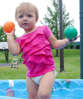Bella Deverney, 2, enjoys tossing balls from one pool to another.