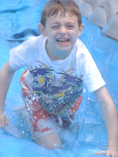 Caleb Brown crawls down the runway after a turn on the water slide.