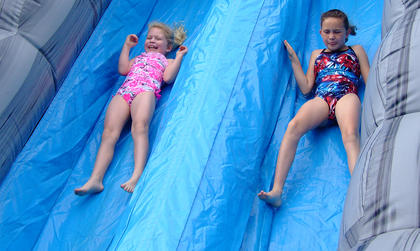 Erica Richardson, left, and Brianna Thomas, 10, are in sync during this run down the water slide.