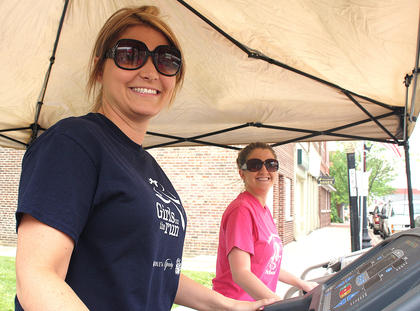Girls on the Run volunteers Hope Dougherty and Davette Mays smile for the camera while making strides on their treadmills.