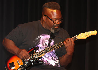 "Daryell Williams plays a bass guitar during a performance by ""Big Dog 1580."" His nieces, Arieyon and Jasmyne Smith, are also in the band. He won second place in the adult division."