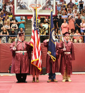 MCHS ROTC senior color guard presents the flags during the national anthem at their commencement ceremony.