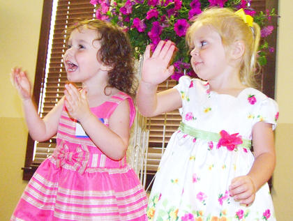 Lauren Worthington (left), 3, and Scarlett Blandford, 3, practice waving to the crowd before the beauty contest begins at the old Bradfordsville School.