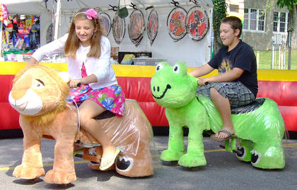Caley James (left), 10, and Cole Shroyer, 11, take a spin on a few of the Zippyland Rides.