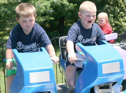 Andrew Bright (left), 3, and Kyle Purdom, 3, enjoy a motorcycle ride. Wesley Purdom, 2, is in the background.