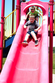 Wesley Purdom excitedly races down the slide.