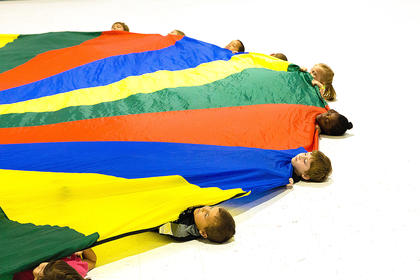 Students relax for a moment under the parachute.