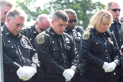 Lebanon officers bow their heads as prayers are said before the burial.