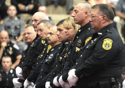 Lebanon police officer stand at attention to honor their fallen chief.