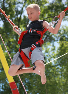 Jacobi Summers, 8, of Bradfordsville enjoys a turn jumping a trampoline while connected to a bungee cord harness.