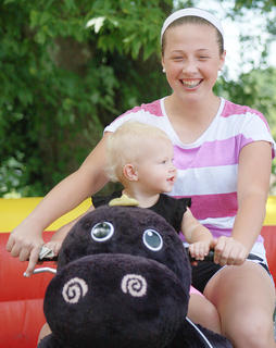 Kaylee Cheatham, 14, and Presley Gribbins, 1, both enjoy the Zippy Land rides on Saturday.