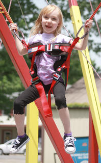 Kyli Greenwell, 5, can't help smiling while on the trampoline-bungee cord ride.