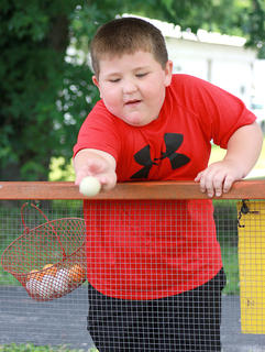 Andrew Bright, 5, tries to toss a ping-pong ball into a glass bowl to win a rabbit during Old Mill Days.