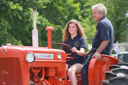 Abigail Yates drives a 1958 Allis-Chalmers tractor as George Gribbins, the owner, enjoys the ride in the parade.