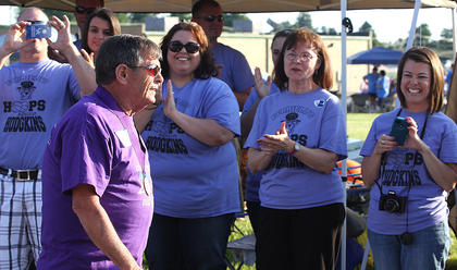 """David Ferriell walks the survivor's lap as his family and members of the """"Ferriell's Hoops Against Hodgkins"""" team cheer him on."""