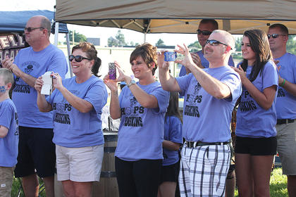 """Members of the """"Ferriell's Hoops Against Hodgkins"""" team take photos and capture video with their phones as David Ferriell passes by during the survivor's lap."""